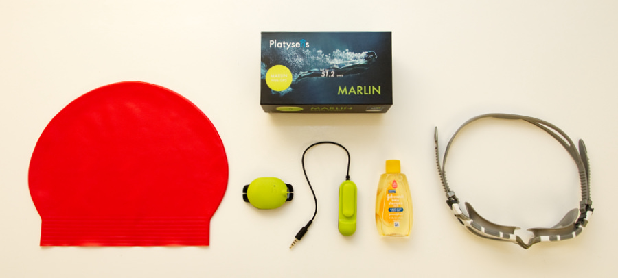 The Platysens Marlin Swim Meter, a swimming cap, goggles, and a bottle of baby shampoo