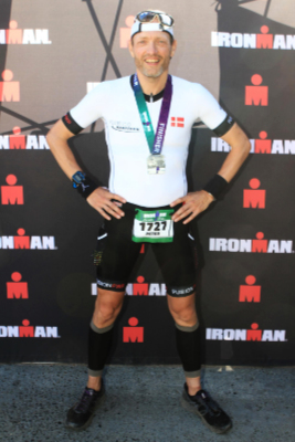 A male triathlete poses in front of Ironman logos