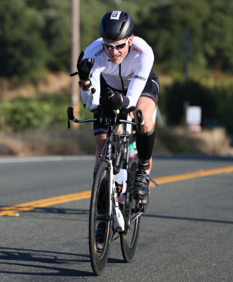 A male triathlete riding a time trial bike outdoors