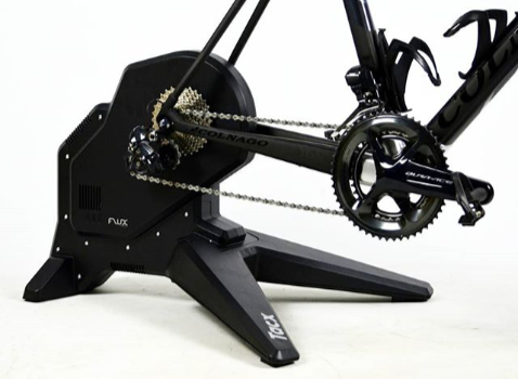 A photograph of a Tacx Flux Smart Direct-Drive cycling trainer with a Colnago bike attached