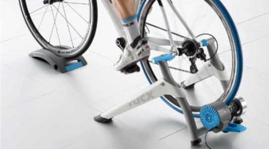 A photograph of the Tacx Flow Smart bike trainer with a road bike attached and a person riding it