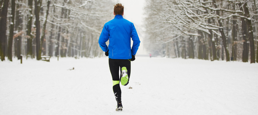 A photograph of a male running outdoors in snow