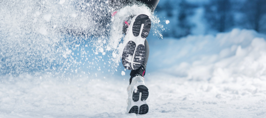 A photograph of an athlete running outdoors in the snow