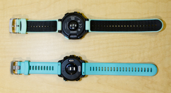 A photo of the backs of the Garmin Forerunner 245 and 235 running watches