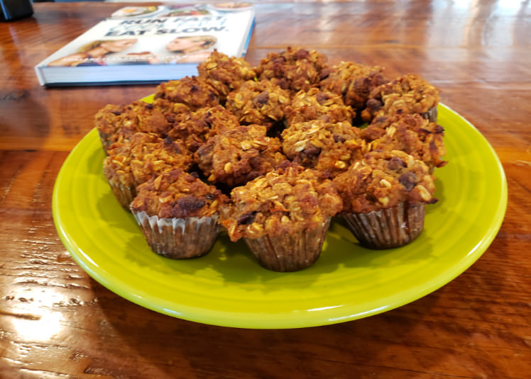 A green ceramic plate filled with apple and carrot mini-muffins