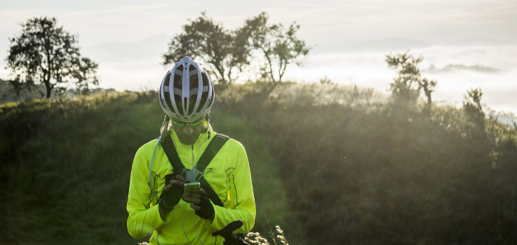 A cyclist wearing a helmet takes a break and checks his phone
