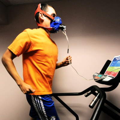 A person running on a treadmill wearing a face mask while taking a Vo2 max test indoors