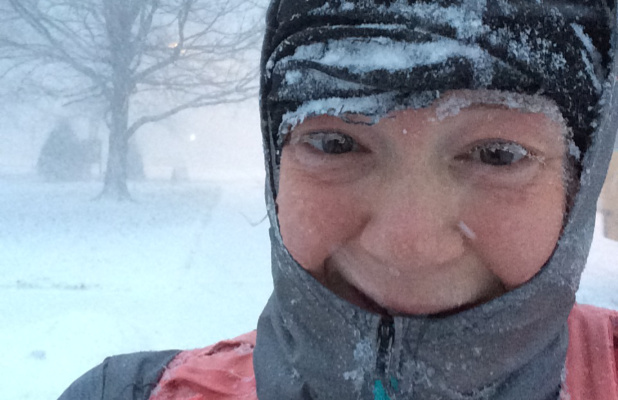 A photograph of a woman outdoors in a winter storm with ice on her clothing