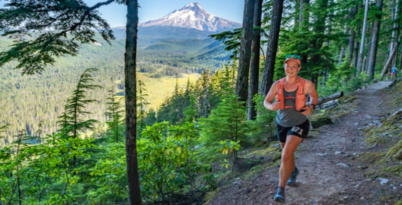 A female ultrarunner runs on a trail with view of Mt. Hood in the distance