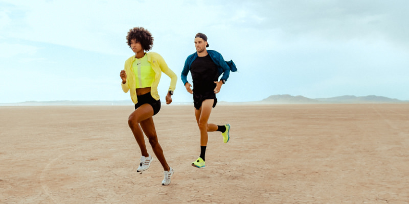 A male runner drafts behind a female runner using a Stryd running power meter