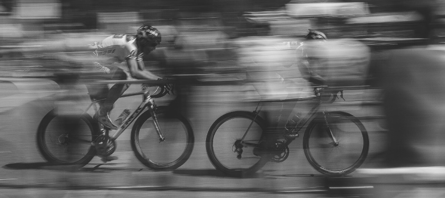A black-and-white photo of two road cyclists moving quickly on their bikes
