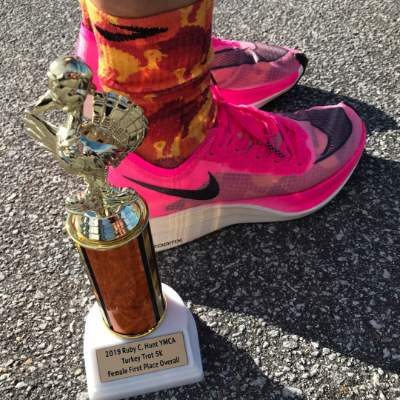A photo of a first place 5K turkey trot trophy with a person wearing pink Nike VaporFly ZoomX Next % running shoes behind it