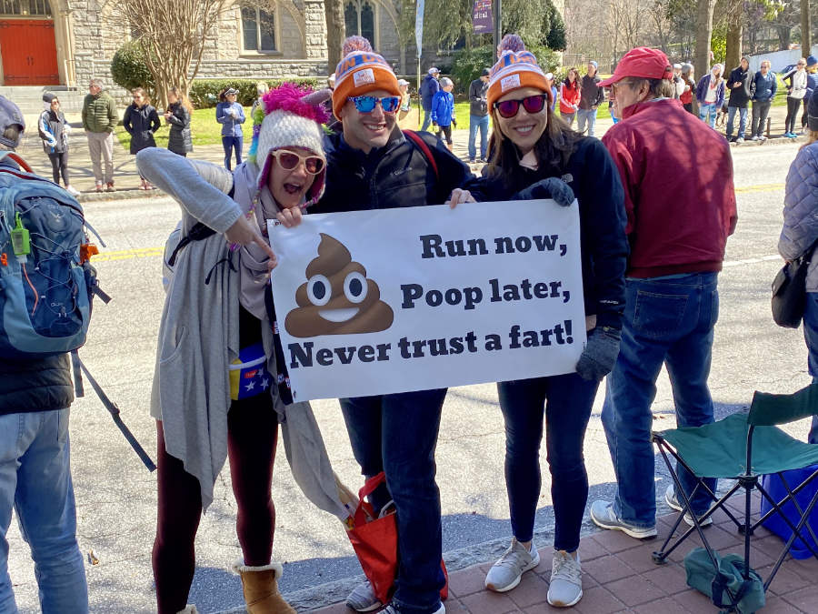 Spectators at a running race with a humorous sign to cheer on the runners