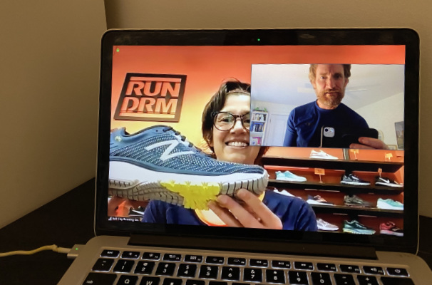 A photograph of a laptop with a Zoom call between a running shoe expert and a client