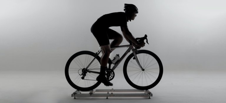 A road cyclist rides on indoor rollers